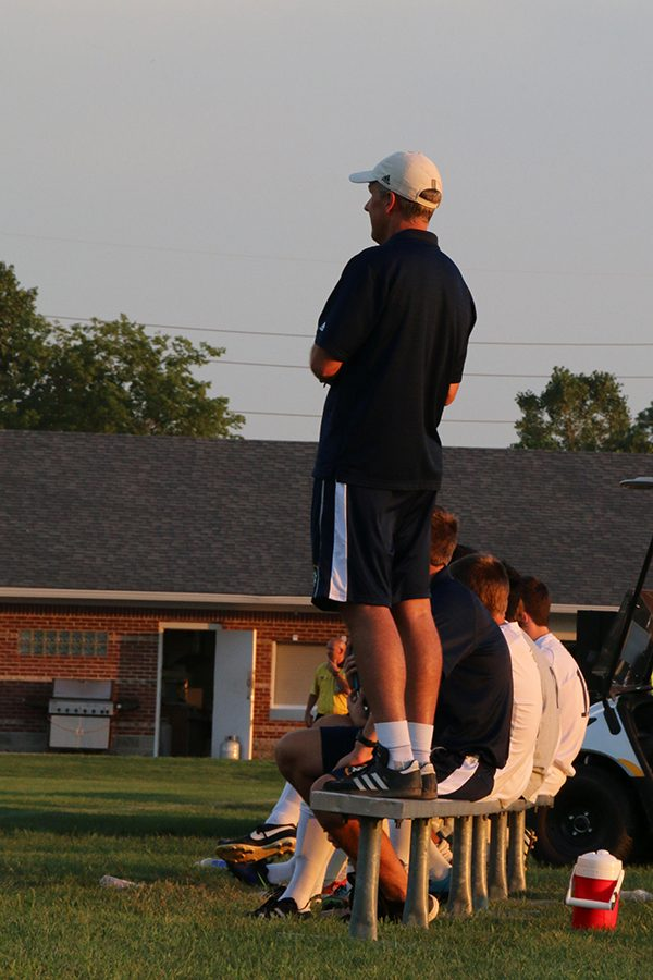 During a regular season boys' soccer game, Head Coach Mr. Paul Schroeder takes in the action.