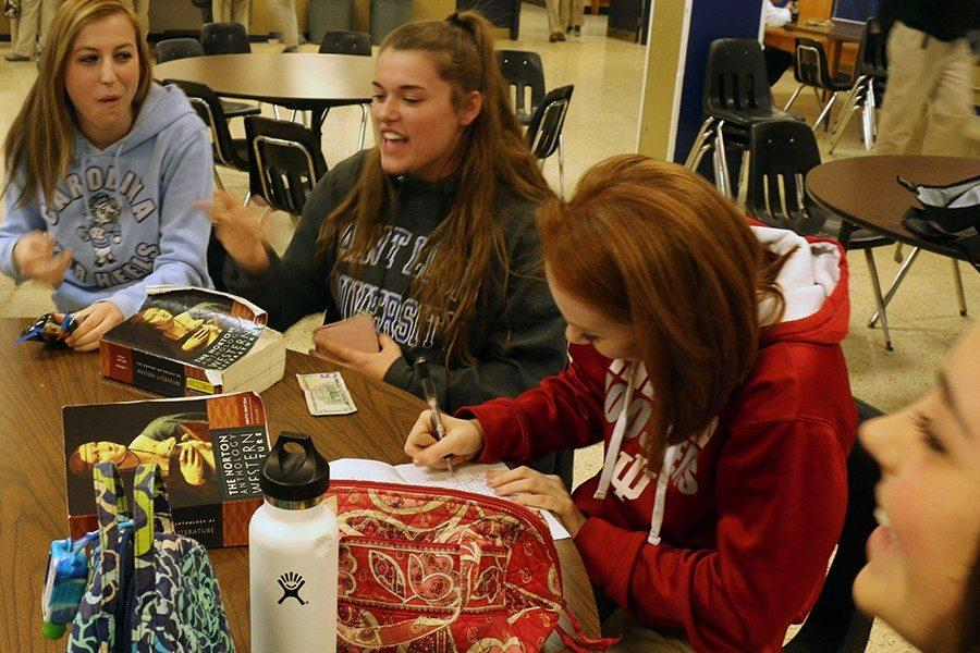 Seniors Lauren Buday, Morgan Klase and Kaylyn Krauss eat lunch and work on homework during G period on Feb. 2.