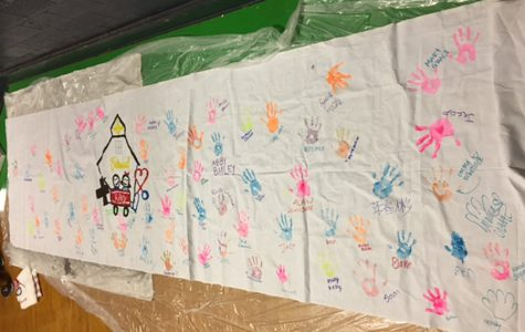 At the March 4 dance marathon in the auxiliary gym, participants added their hand prints to a banner.