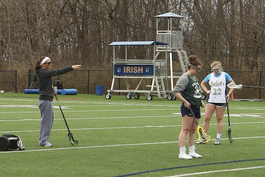 Assistant Coach Mrs. Katie Erbe directs seniors Mallory Johnson, Abbi Sherfick and Taylor Trieloff in a drill last Tuesday.