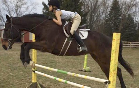 Freshman Diane Houk jumps her horse in preparation for her upcoming competitions. She owns two of her own horses, named Zorro and Double.