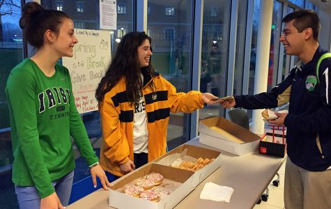 Juniors Anna Mattingly and Mary Ann McGinley sell donuts to senior Max Eslava before school on March 31 to fund this year's prom.