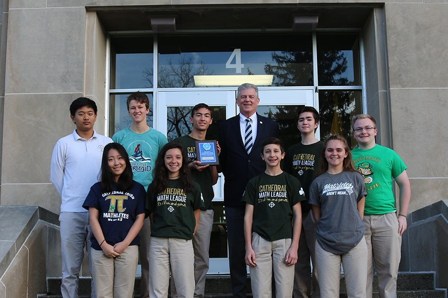 Members of the Regional champion Math League team pose with Principal Mr. Dave Worland at the school's main entrance.