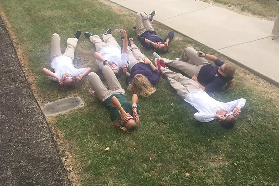 On+the+lawn+outside+Loretto%2C+students+recline+to+get+the+best+view+of+the+partial+solar+eclipse.+