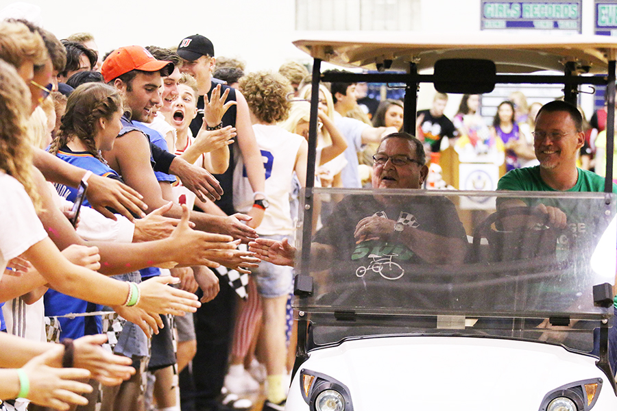 With theology teacher Mr. Marc Behringer '84 as his driver, Fr. John Zahn takes a lap around the Welch Activity Center gym floor at last spring's Irish 500. Fr. Zahn passed away over the weekend of Aug. 26-27.