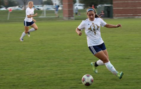During a regular season match, senior Camryn Wylam moves the ball down the pitch.