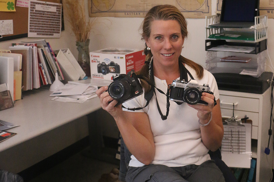 Photography teacher Ms. Joellen Desautels poses in her classroom, Cunningham 1220, with the types of cameras for which she seeks donations.