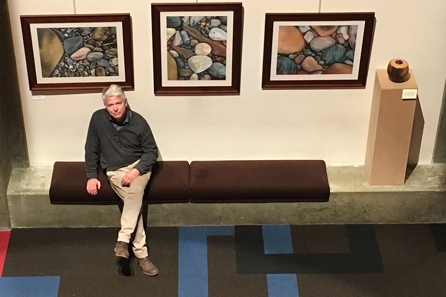 Art teacher Mr. Jon Kane poses in front of several of his pieces that are part of an exhibition at Clowes Hall on the Butler University campus.
