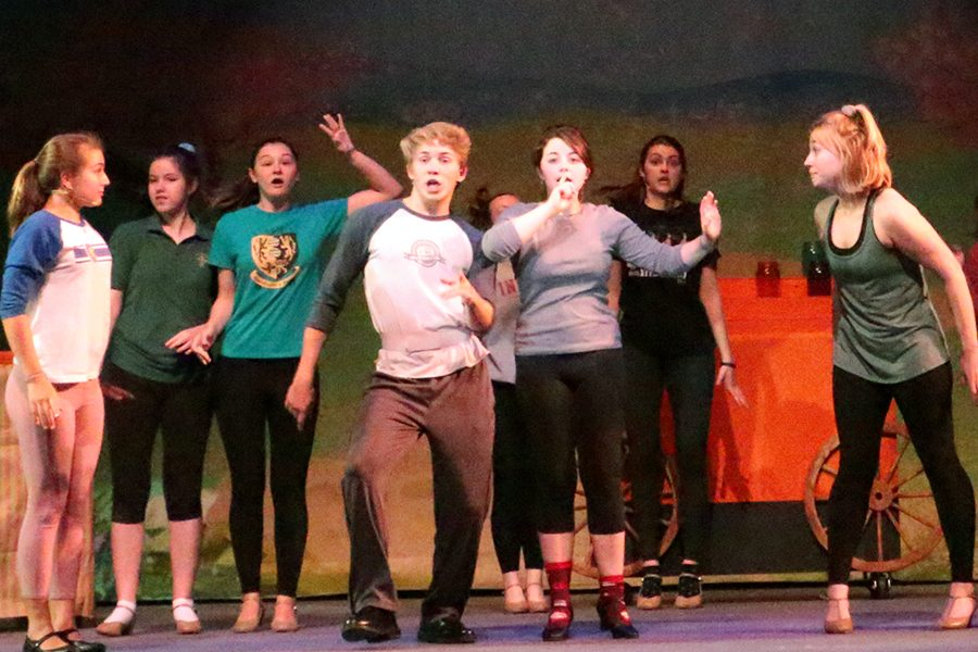 Senior Ethan Gogel leads the cast during a rehearsal of