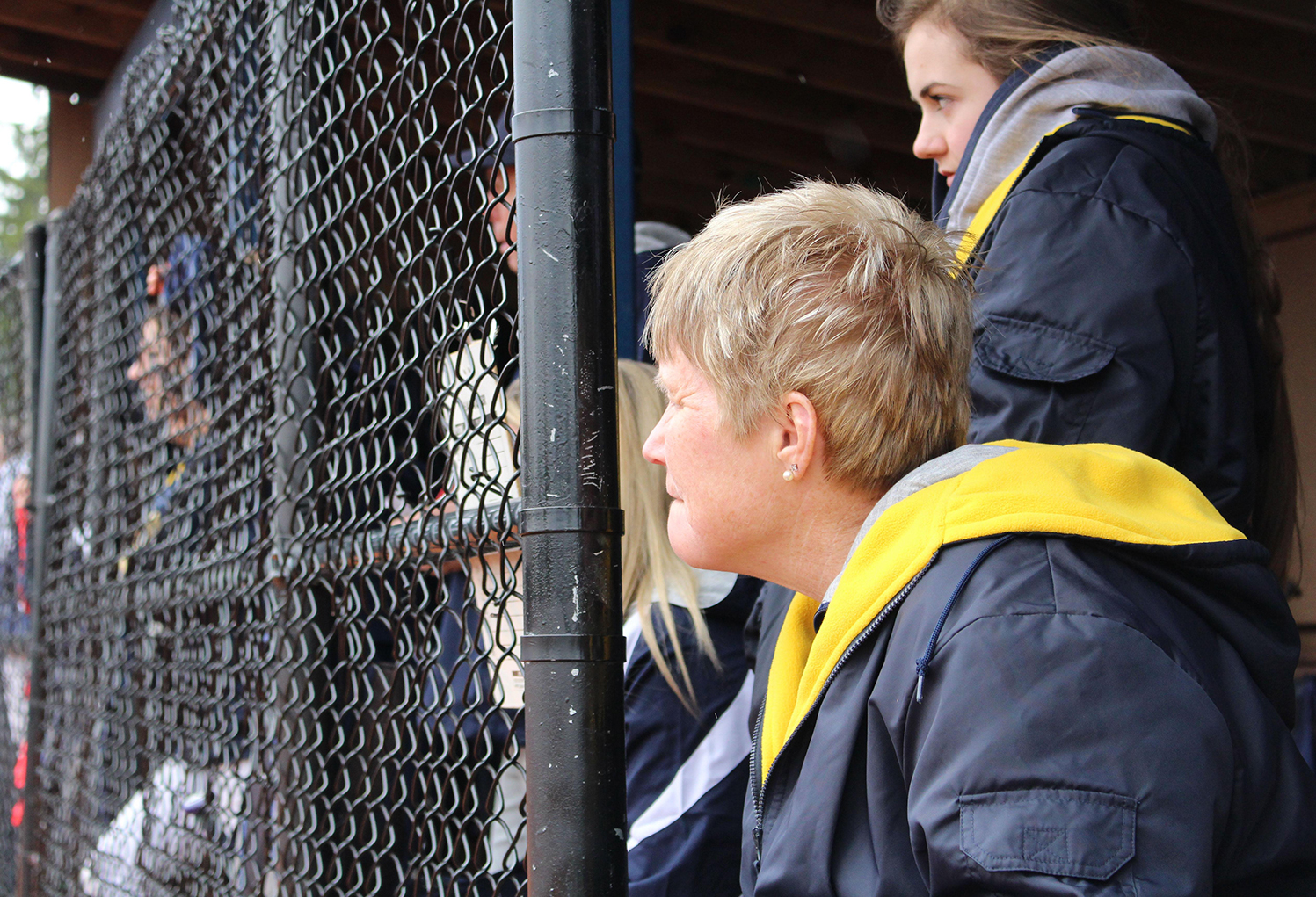Physical education department chair and varsity softball assistant coach Mrs. Linda Bamrick takes in the action from the dugout.