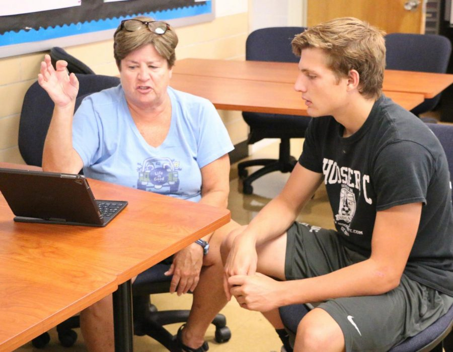 English teacher Ms. Laurie O'Brien assists senior Nick Kolosso with his college essay at the college application boot camp last August. The camp alowed seniors to get a head start on their college applications and essay writing. English teachers were available to give advice regarding their college essays.