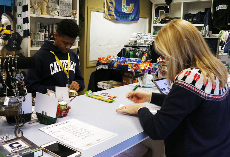 A student makes a purchase at the bookstore during E period on Dec. 5.