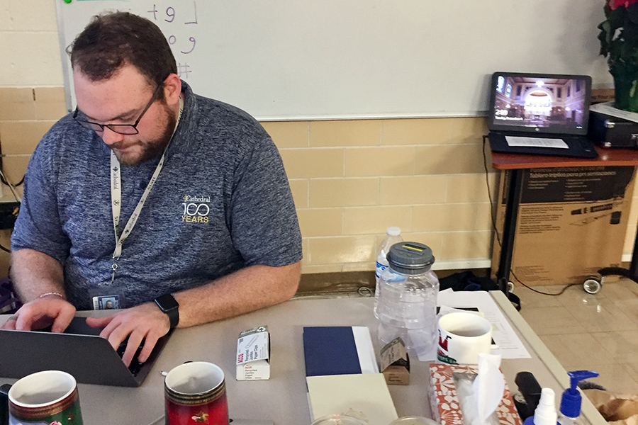 Theology teacher Mr. Matt Cannaday works as his desk in his classroom in Kelly Hall.