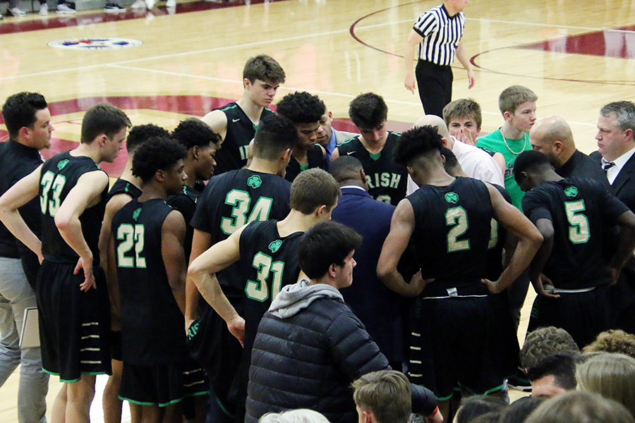The men's basketball team gathers around the coaching staff during the Dec. 1 game against Brebeuf Jesuit.