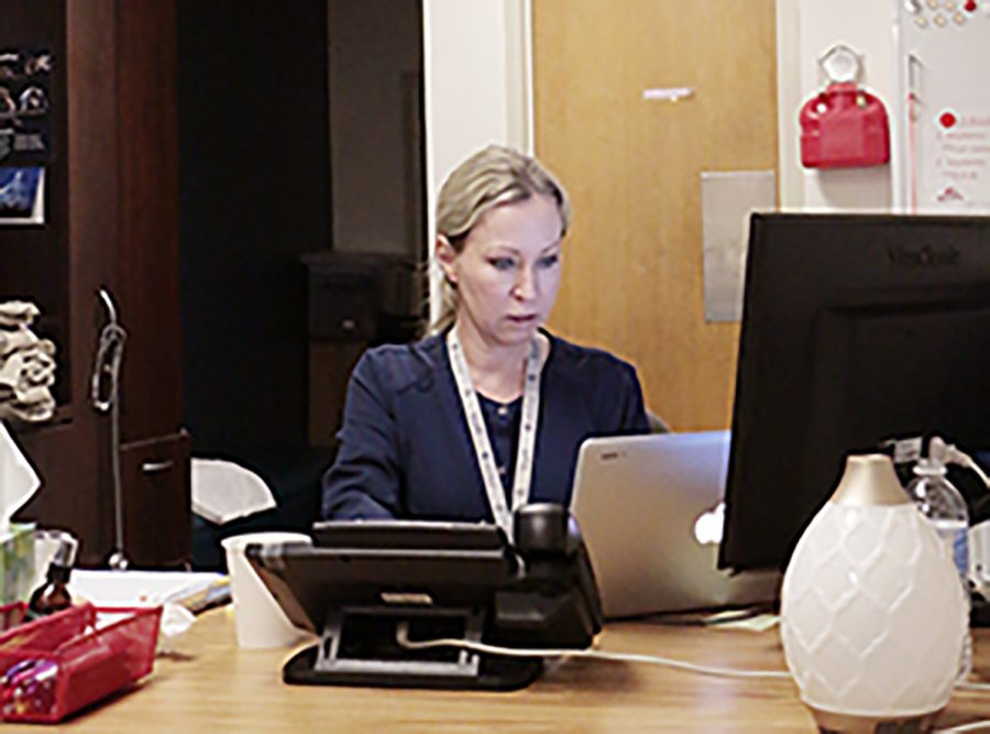 Nurse+Mrs.+Courtney+Jennings-Sood+works+at+her+computer+in+her+office+on+the+first+floor+of+Kelly+Hall.