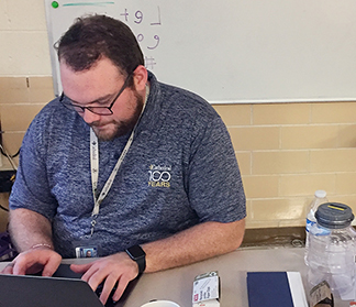 Theology teacher Mr. Matt Cannaday works at his desk in his classroom on the first floor of Kelly Hall. In June, Cannaday will travel to Peru to help lead 13 students on a mission trip.