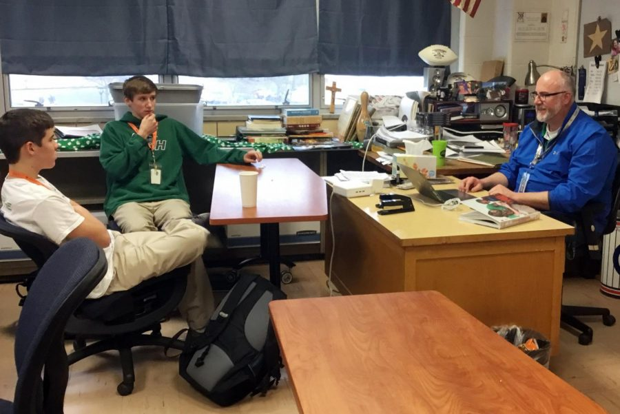 In his classroom on March 29, social studies teacher Mr. Anthony Ernst talks to sophomores Isaac Michael and Levi Wojtalik.