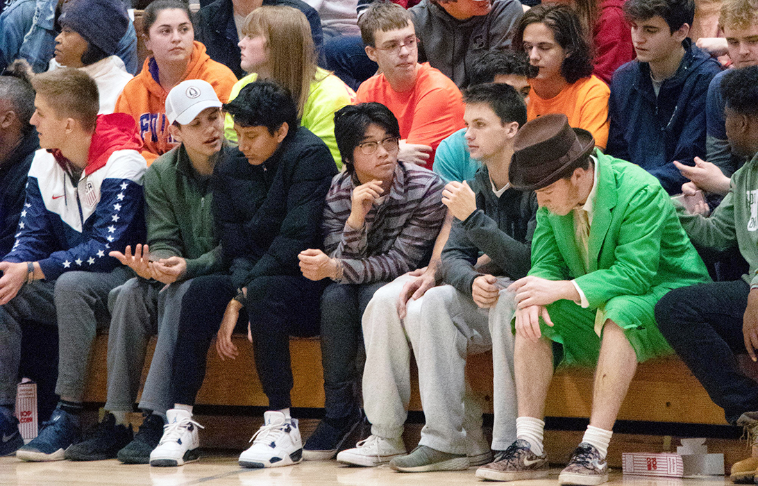 At a men's basketball home game against South Bend Riley, junior Andrew George sits in the second row of the student section during an Irish time out. George attends every home event that he can, always sporting the theme and cheering on the Irish.