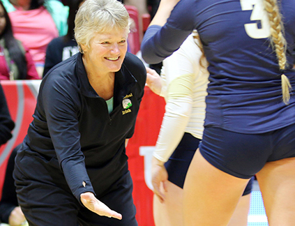 Former women's volleyball Head Coach Ms. Jean Kesterson, who has been inducted into the National Fall of Fame, ended her coaching career on a high note. She led the varsity team to an undefeated season two years ago, and the squad was named National champion. She gives a high five to Payton White at Ball State's Worthen Arena, the site of the Class 4A State championship match, where the Irish defeated Crown Point to bring home yet another championship tropy.