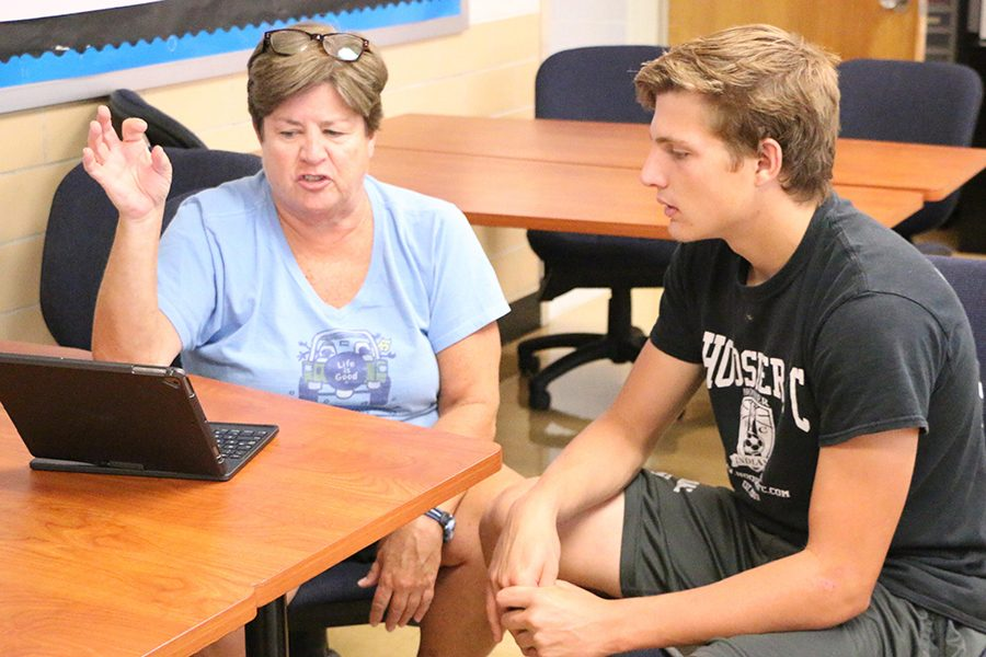 English teacher Ms. Laurie O'Brien works with senior Nik Kolosso during the college essay boot camp in August. O'Brien and math teacher Mrs. Rachel Ludington will teach the last SAT prep class of the school year on March 11.