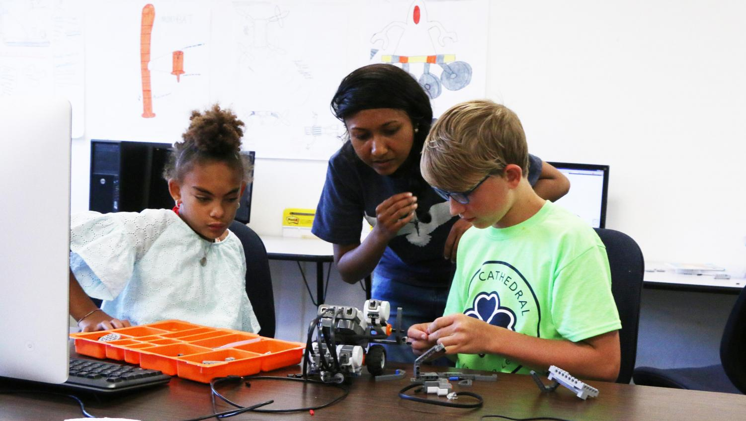 STEM teacher Ms. Ria Periera works with students on a project during last summer's Camp Cathedral.