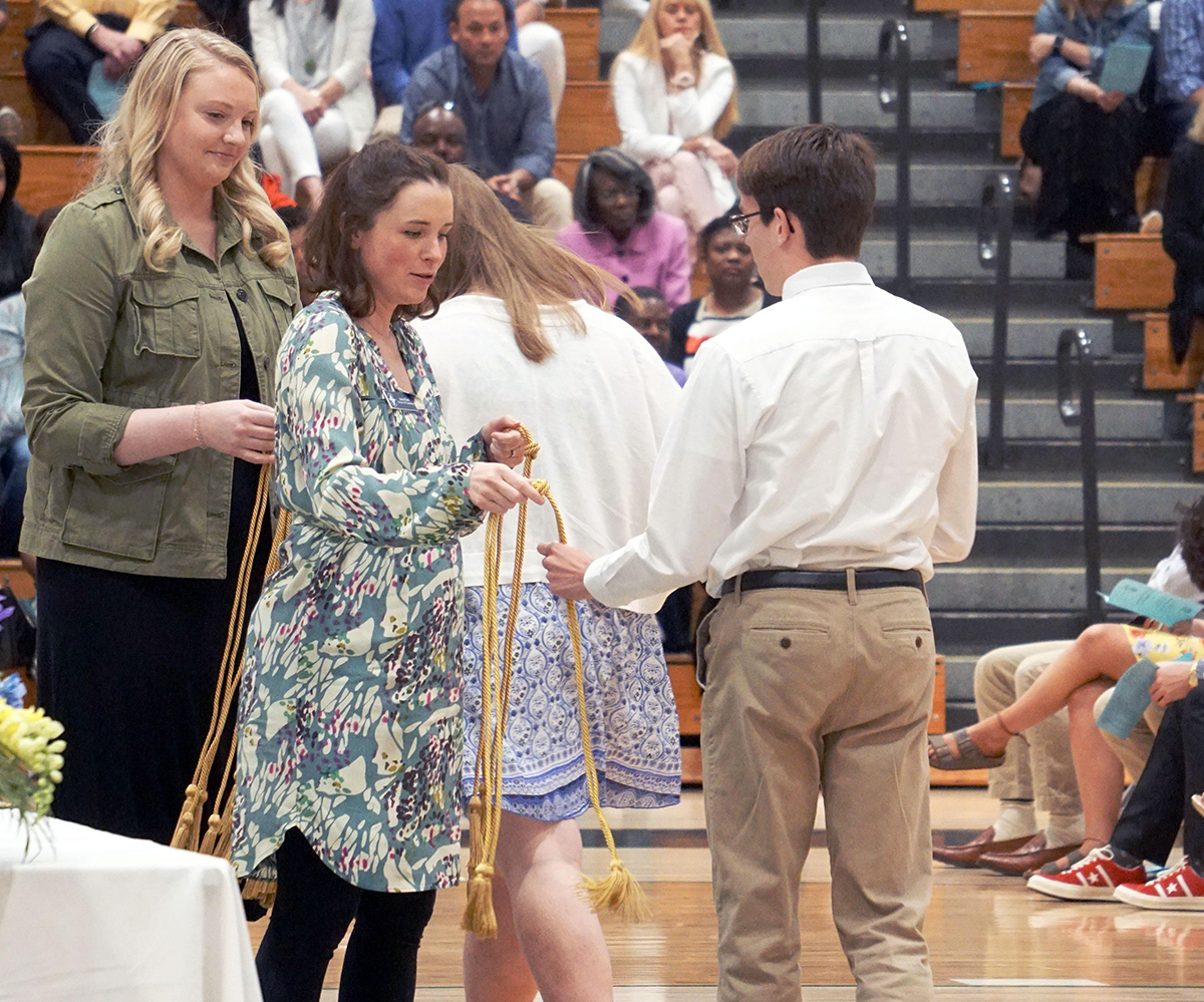 From left, counselors Mrs. Mary Hemer '09 and Mrs. Katz hand out membership cords to the National Honor Society inductees on April 28 in the Welch Activity Center.