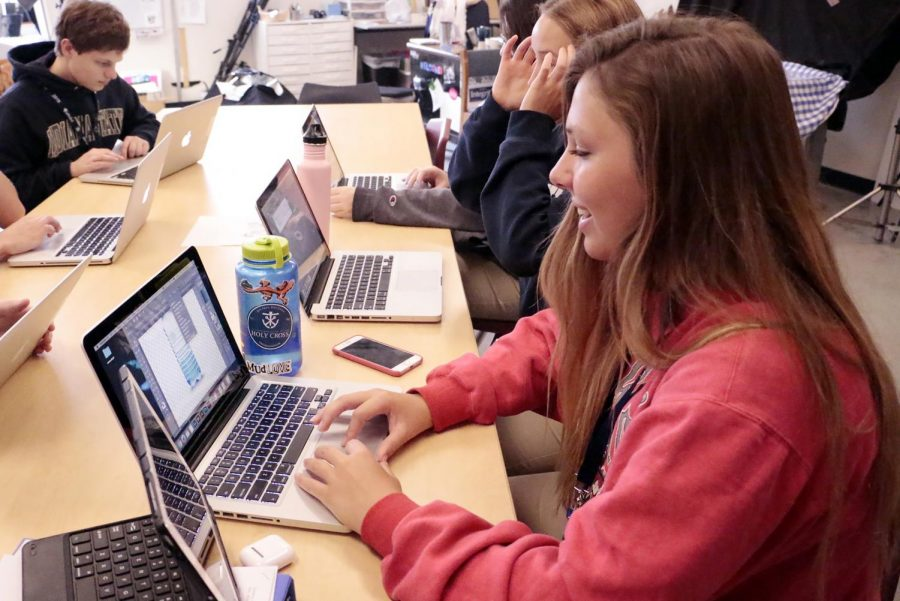 Senior Emma Doyle works on her laptop on another graphic design class project.