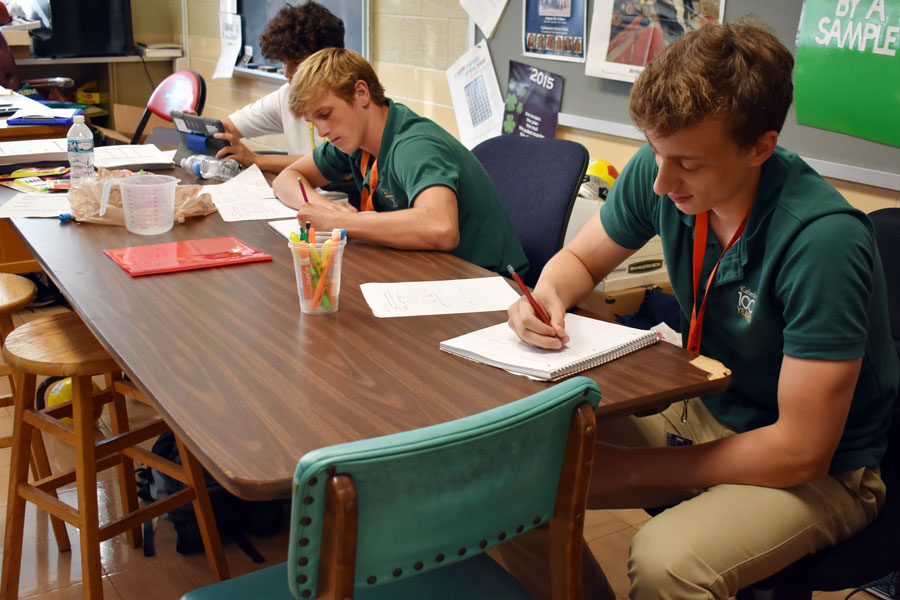 Junior Jake Kazan, far right, takes notes during Mr. Howard Fogel's E period chemistry class.