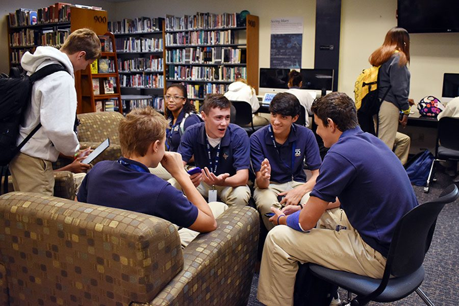 Before school on Aug. 15, a group of freshman boys gathers in the library. The library opens each morning at 7.