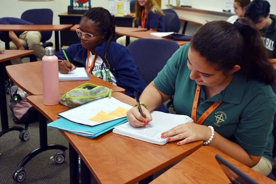 Ana Arce-Rameriz, right, takes notes during her E period English class in Loretto Hall.