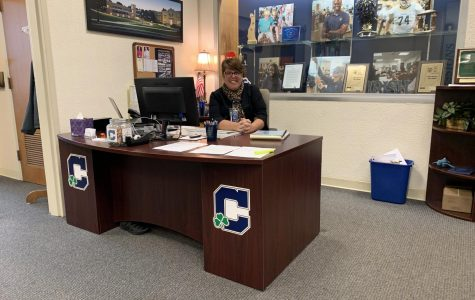 Mrs. Maribeth Cloud works at her desk in the admissions department at the main entrance of Kelly Hall.