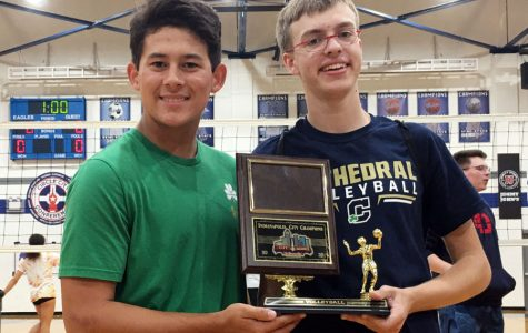 Senior Andrew George, right, shows off the women's volleyball City championship trophy.