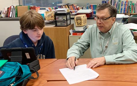 In his classroom, Mr. Gary Spurgin assists a student with an assignment.