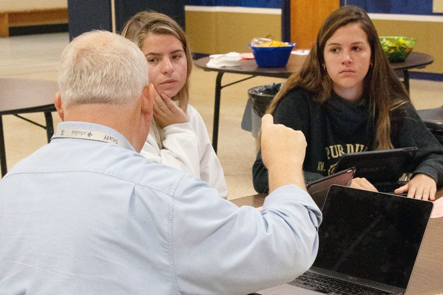 At+the+August+college+boot+camp+for+the+Class+of+2020%2C+director+of+counseling+Mr.+Duane+Emery+provides+essay+tips+to+seniors+Payton+Snyder+and+Cole+Spau.