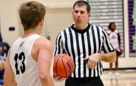 During the men's varsity basketball game on Dec. 7 against Brebeuf Jesuit, an official prepares to hand the ball to senior Ryan Trusler.