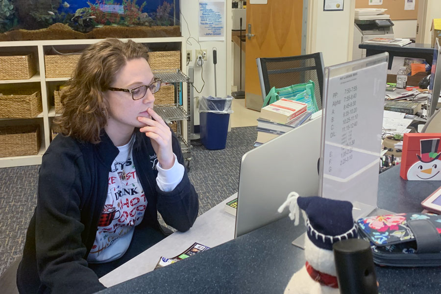 Library/media assistant Ms. Alannah Cataldo works at her desk. She provided information for how students could access books and other materials during eLearning.