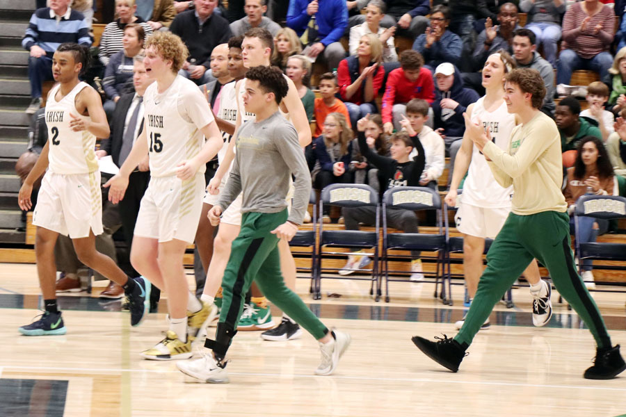 Junior Camden Jordan, wearing a gray long-sleeved T-shirt, and his teammates celebrate a 60-55 win over Roncalli on Jan. 10.