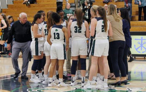 The women's basketball team gathers around its coaches during the varsity game in December against Zionsville.