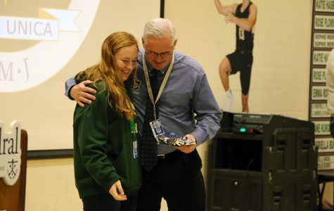 Senior Ellie Sheddy presents Mr. Mark Matthews with his Spirit of Holy Cross award at the Jan. 31 Winterfest assembly.