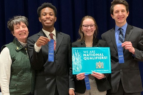 Speech and debate Head Coach Mrs. Jeanne Malone stands with three of the four qualifiers for Nationals: Victory Sampson, Lauren Dubbink and Nick Grill. Madison Ackley is not pictured.