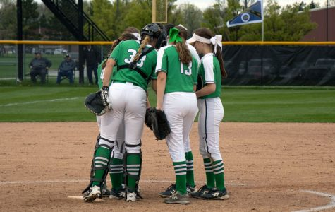 Grace Lorsung and her fellow softball team members gather on the mound during a varsity game last season.