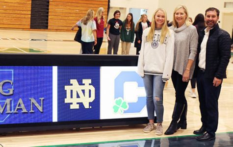 Senior Megan Coleman stands with her parents during the fall signing ceremony, which recognized seniors who had signed a commitment letter to their university.