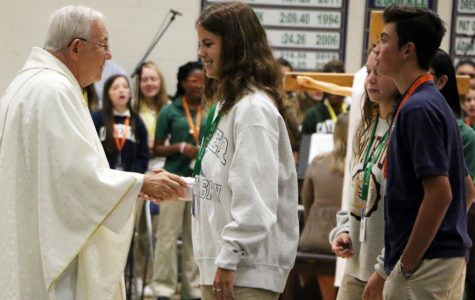 Fr. Jeff Godecker greets senior Lila Welch at Mass earlier this school year. Fr. Godecker celebrated Easter Mass in the school chapel, and that Mass was live streamed through the school's Facebook page.