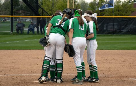 In her catcher's gear, senior Grace Lorsung meets with her teammates during a regular season game last year.