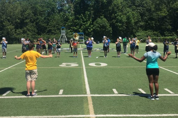 The drum majors lead a recent Pride of the Irish practice on the football field.