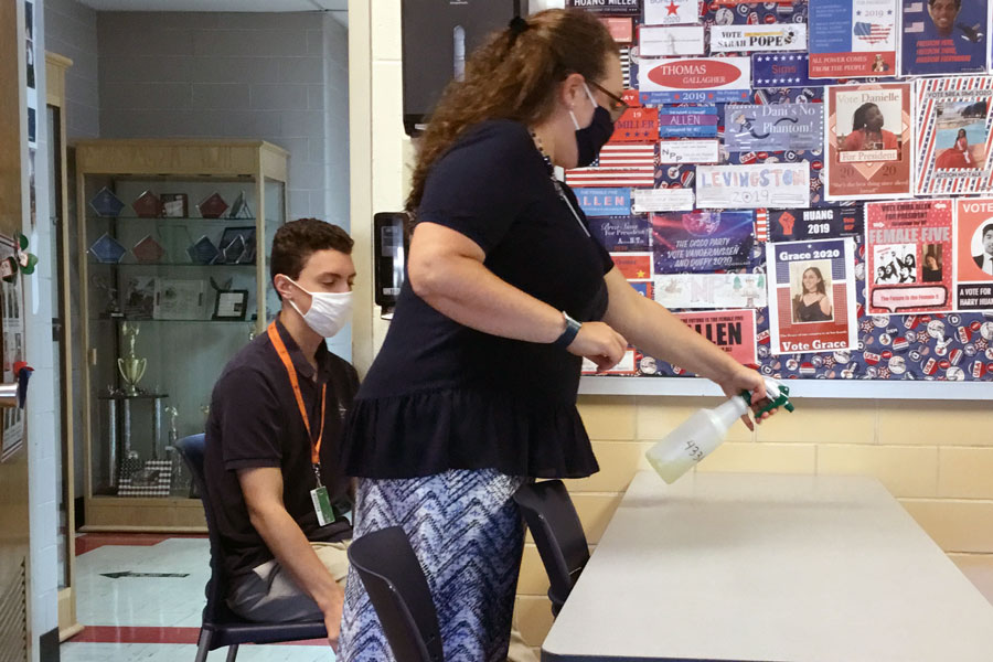 Social studies teacher Mrs. Jill Twilleager sprays disinfectant on a desk in her classroom during period F on Sept. 8.