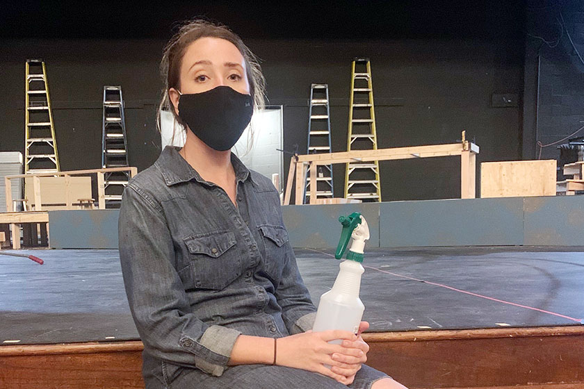 Disinfectant spray bottle in hand, theater director Ms. Maria Souza sits in the auditorium during before E period before her tech theater class.