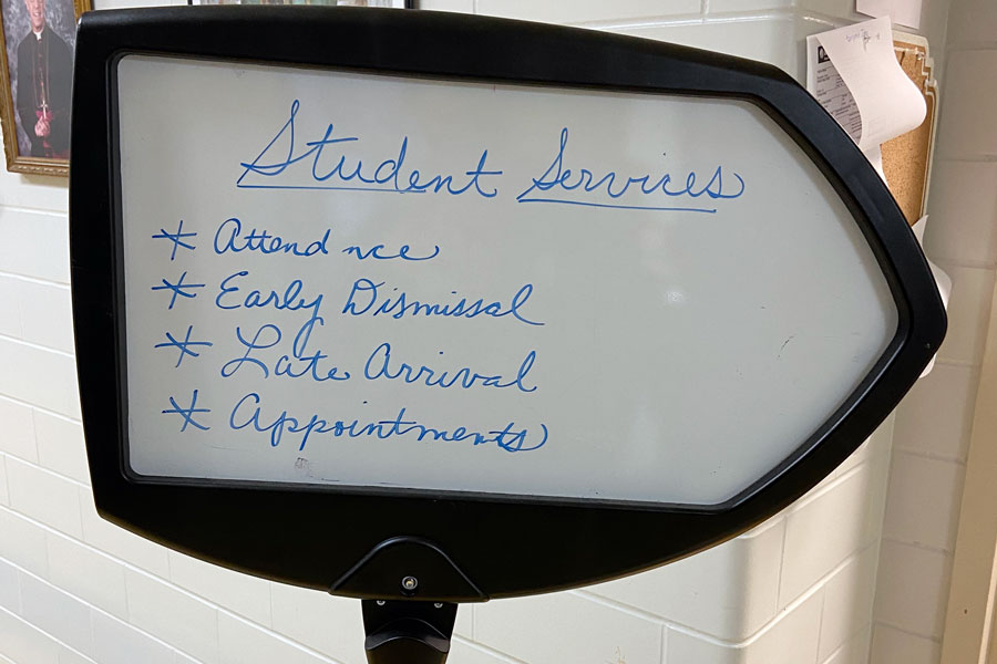 A sign in Kelly Hall directs students to the student services suite.