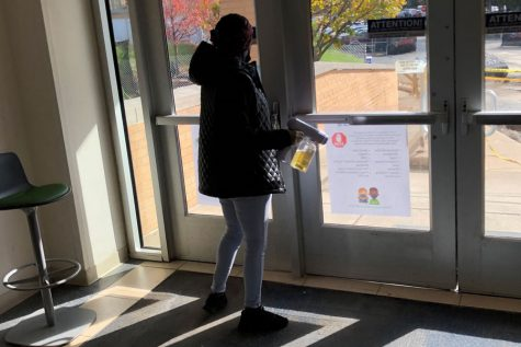 Immediately after a passing period on Oct. 29, an EMS staff member disinfects the door handles on the southwest entrance of Kelly Hall.