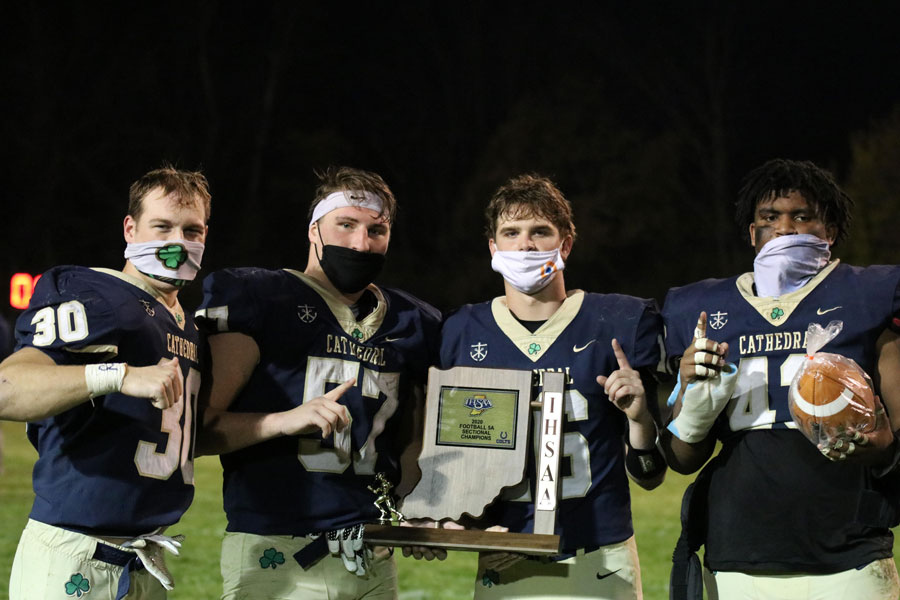 Varsity+football+players+show+off+the+Sectional+championship+trophy.+